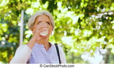 senior woman drinking coffee at park - old age, retirement...