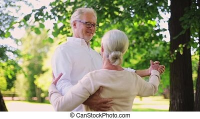 happy senior couple dancing at summer city park