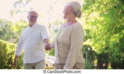 happy senior couple walking at summer city park - old age,...