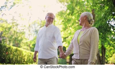 happy senior couple walking at summer city park - old age,...