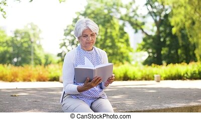 senior woman reading book at summer park - old age,...