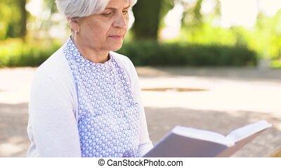 senior woman reading book at summer park - old age,...