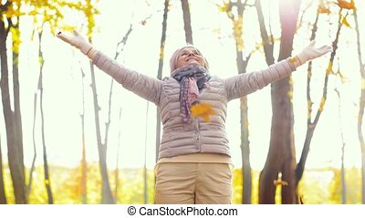 happy senior woman throwing autumn leaves up - old age,...
