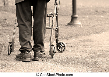 Old age - Senior man taking a walk in a park with the aid of...
