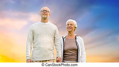 happy senior couple holding hands over evening sky