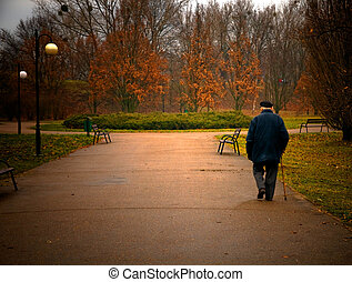 Old aged man walks in park - Old age concept. Man walks in...