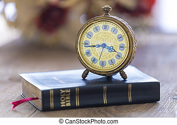 Old alarm clock on Holy bible with flowers on wooden table