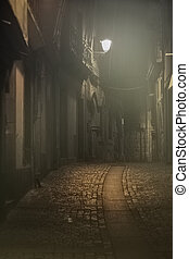 Old alley in a foggy night