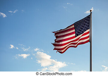 Old American flag blowing in the wind on the blue sky.
