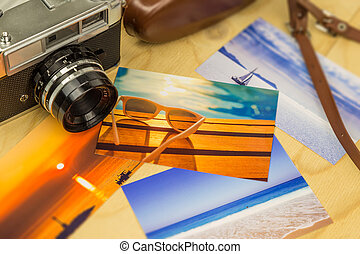 Old analog camera with colorful summertime pictures, on wooden surface
