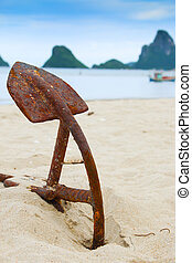 Old Anchor on the beach with ship and mountain as background