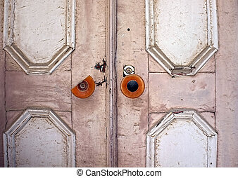 Old ancient door with a broken knob