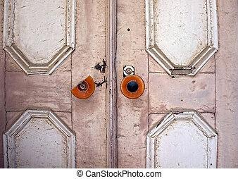 Old ancient door with a broken knob