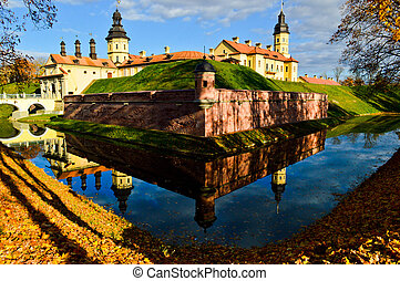 Old, ancient medieval castle with spiers and towers, walls of stone and brick surrounded by a protective moat with water in the center of Europe. Baroque style architecture
