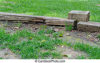 old and abandoned wooden fence in a meadow covered with grass