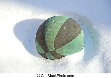 old and aged rubber playing ball on snow in garden