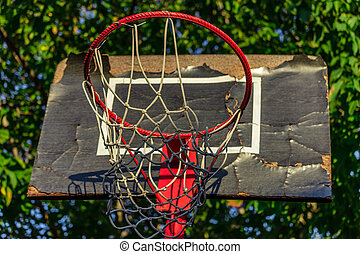 Old and damaged basketball hoop with cage,tree and house in the background,view from below