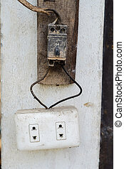 Old and danger electric plug on wall.