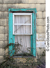 turquoise window - old and heavily decayed building exterior...