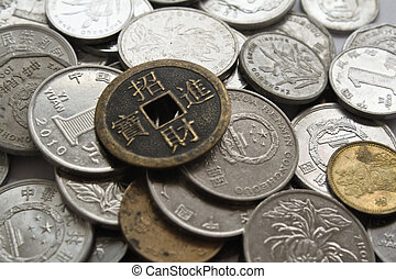 old and new chinese money - an ancient chinese coin sits...