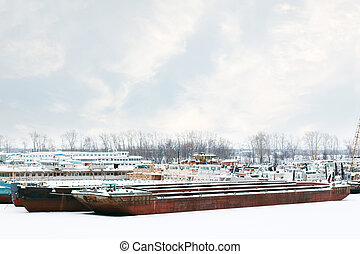 Old and rusty big freight and passenger ships on frozen river