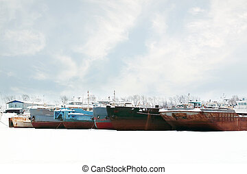 big freight ships on frozen river at winter