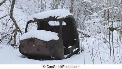 old and rusty car body in the forest in winter