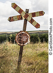 Old and rusty railroad sign with stop letters.