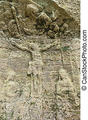 Old and weathered relief of Jesus Christ in a sandstone rock
