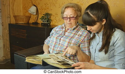 Old and young woman looking at family photo album on sofa at home