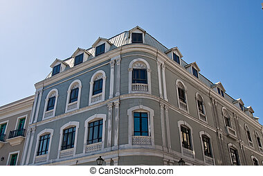 An old grey building under blue sky with many windows