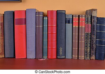 Old antique books background. The ancient books on an orange and claret  background