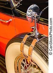 old antique car's spare wheel with rear view mirror