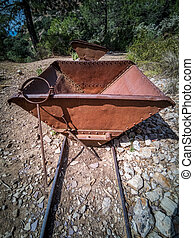 Old antique mine dump car and track in the wild