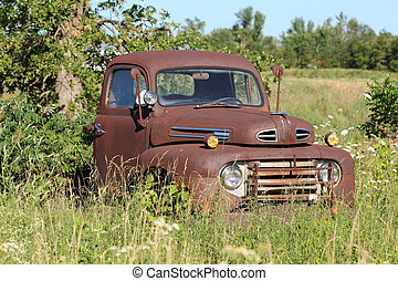 A very old antique truck has been left out in the weather to rust away and become the home to generations of mice.