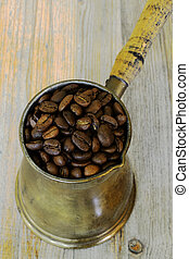 arabic coffee pot on wooden background with beans