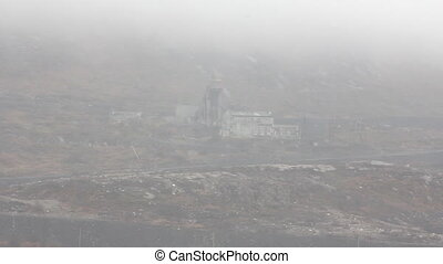 Old Arctic mine extracting Nickel ore in fog, on hillside