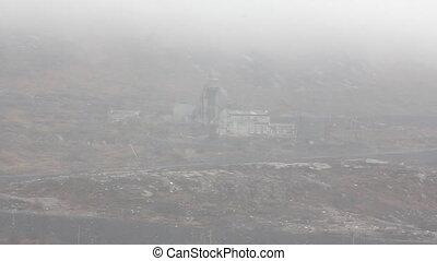 Old Arctic mine extracting Nickel ore in fog, on hillside