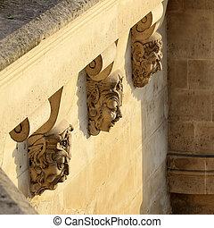 Old art masks on a bridge in Paris