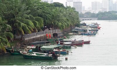 Old asian boats in city channel, Haikou, China