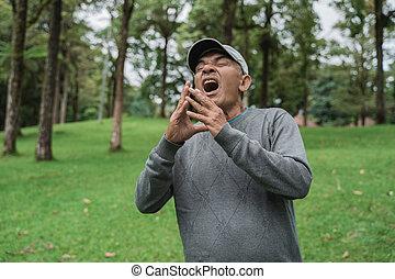 old asian man sneezing having a flu