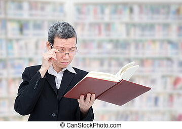 Old asian woman reading book having problem with her eyes