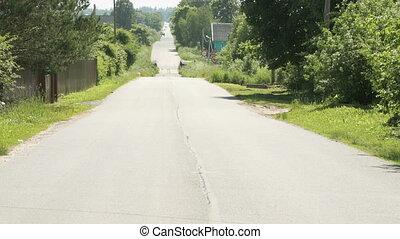 Old asphalt road in village passes through bridge