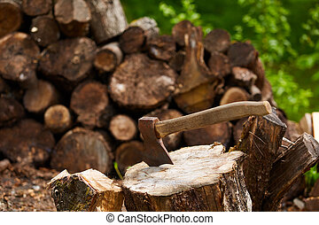 Old ax on log and firewood in the background