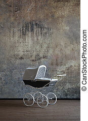 Old baby stroller in worn environment and wooden floor
