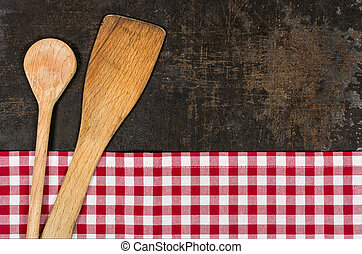 Old baking tray with a red checkered tablecloth and cooking utensils