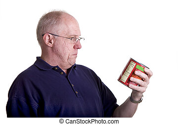 Old Bald Man Reading Nutrition Label - An older bald man...