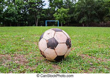Old ball, football on green grass