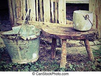 broken bucket and an aluminum pan on the wooden stool