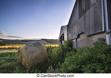 Old barn and hay bales in Summer countryside landscape